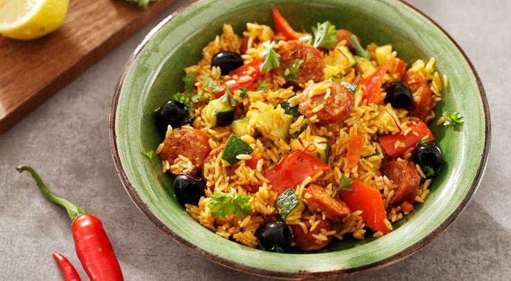 Heerlijk recept voor Spaanse rijstschotel. Ingrediënten: chorizoworst, courgette, puntpaprika en kippenbouillon. Gebruik Lassie Rijke Roerbakrijst wit.