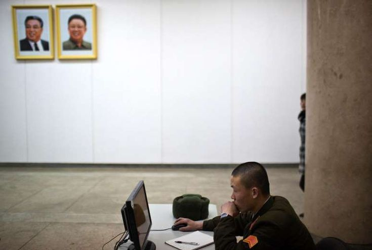 A North Korean soldier works at a computer terminal under portraits of the late leaders Kim Il Sung and Kim Jong Il inside the Grand People's Study House in Pyongyang on March 12.