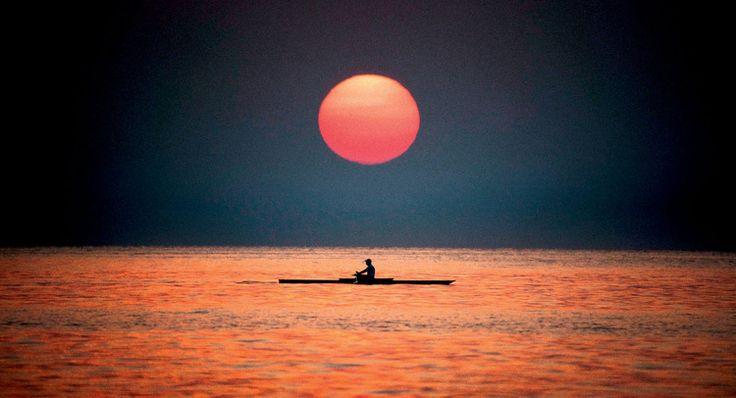 Każdy wschód i zachód słońca jest Twój - to najlepszy moment dnia na fotografowanie. Nie chodzi o samą czerwoną kulę, ale moment, kiedy nisko nad horyzontem słońce rzuca długie cienie. W takim świetle każdy motyw wyjdzie świetnie. Najlepsze światło do fotografowania jest 9 -10 rano i od 17 wieczorem. W południe lepiej leżeć na plaży.Na zdjęciu: Triest, Włochy.Fotografia kajakarzapłynącego po morzu,wykonana z portowegomolo bardzo długimobiektywem, fot. Jacek Bonecki