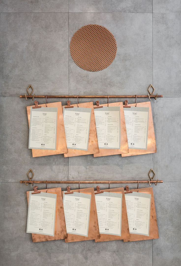 These menus on copper clipboards are hung on a copper pipe attached to the wall of a restaurant in Valencia.