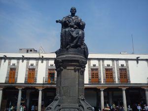 Aquí, la estatua de Doña Josefa Ortiz de Domínguez, al fondo, el Portal de los Evangelistas en la Plaza de Santo Domingo; en 1890 se colocó la escultura de la Corregidora, obra del escultor italian...