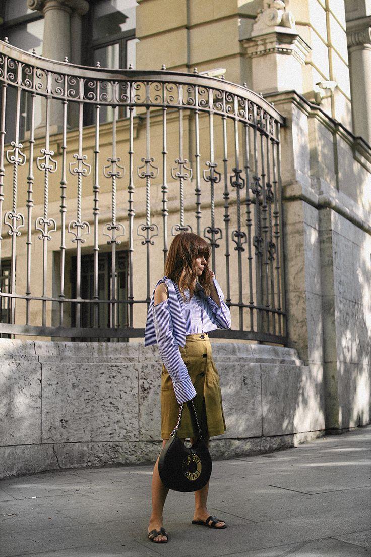 Nisi is wearing: Loewe Joyce Bag, Hermès Oran sandals, cold-shoulder blouse, midi skirt - teetharejade.com