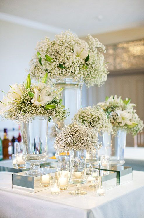 Floral arrangements of baby's breath and white lilies in different size vases are arranged to create depth.