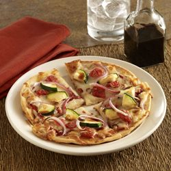A vegetable pizza recipe starts with flatbreads topped with sauce, cheese, tomatoes and zucchini