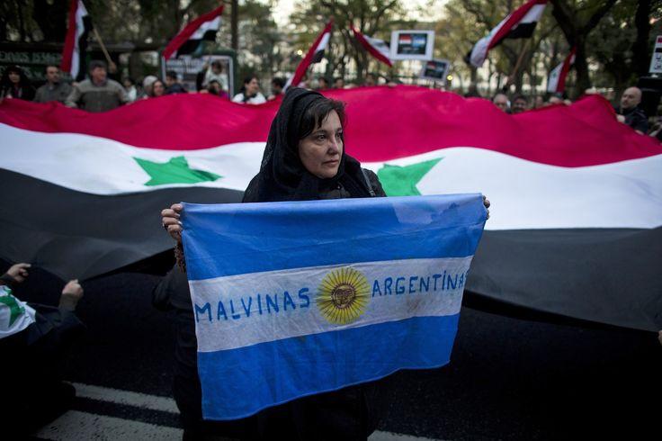 """Una mujer siria sostiene una bandera argentina con las palabras """"Malvinas Argentinas"""", en referencia a las Islas Malvinas en disputa, frente a una gran bandera de Siria durante una manifestación en..."""
