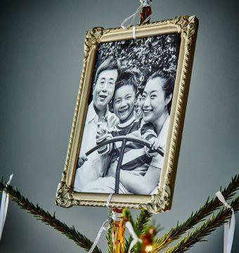 Zarámovaná rodinná fotografia na vrchu vianočného stromčeka.