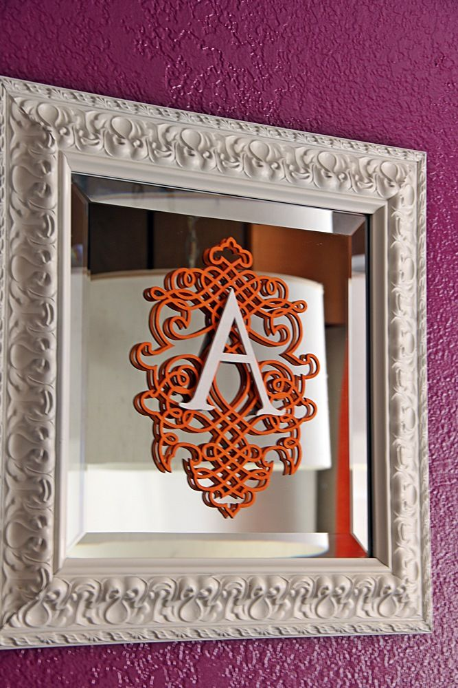 laser cut wood design painted orange with wood letter mounted in center