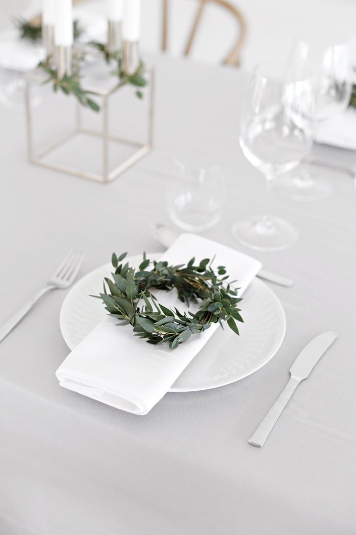 Minimalistic Christmas table setting in white with a fresh green wreath. (Source: Stylizimo, Photo: Nina Holst)