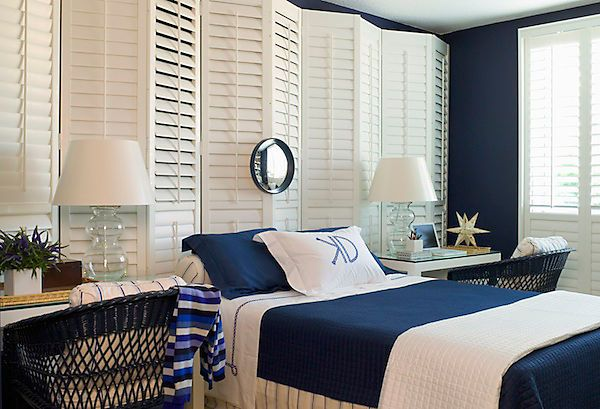 Love the use of 2 small desks PLUS wicker chairs on each side of the bed. Plus, folding screens of shutters make a great headboard and make an instant coastal look.