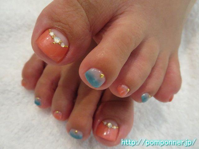 名古屋市緑区 ネイルサロン ポンポネのネイルデザイン。天白区近くの人気サロンです。夏らしい色合いのフットネイルです。親指はパールオレンジで逆フレンチを作り、境目をスタッズ、オパールのストーンで飾りました。他の爪は同じオレンジ、パールブルーでグラデーションを作り、根元はスタッズで飾りました。