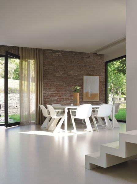 Muri in mattoni e vetrate a luce unica per il lato della casa che si affaccia sul giardino. Il tavolo è su disegno, le sedie sono anni '70, sulla parete un'opera di Pierpaolo Calzolari