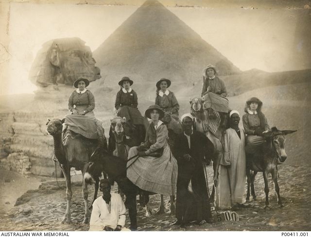 Members of the Australian Army Nursing Service, pictured on camels in front of the Sphinx and pyramids. AWM P00411.001