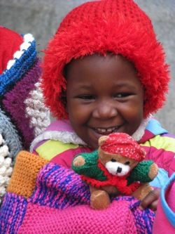 A Re Boneng Creche - Happiness is..... a warm hat, a cosy blanket to keep me warm and a cuddly toy of my very own.  www.knit-a-square.com/