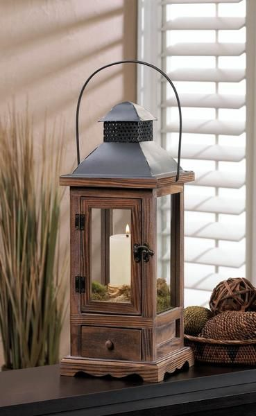 "Candleholders & Candles Home Locomotion Light up your nights with this small lantern thats big on charm. The wooden framework gives way to a black metal roof with a hanging handle, and below is a neat pullout drawer. Candle not included. 18"" high with handle. Item weight: 2.20lbsItem dimensions: 6.00"" W x 15.88"" H x 6.00"" LMaterials: Wood - Pine, Wood - Mdf, Iron, GlassUPC: 849179023133"