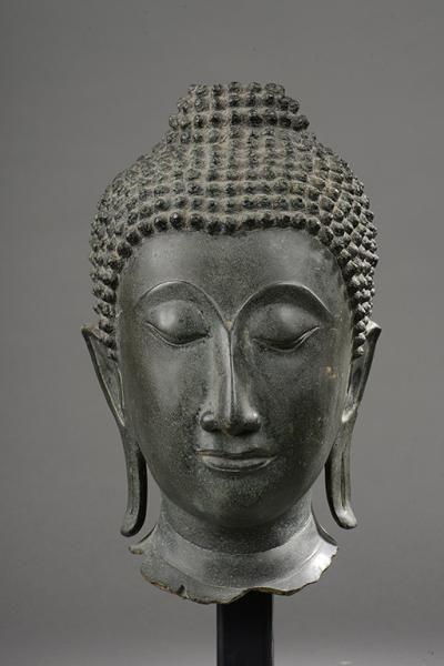 Tête de Bouddha à la beauté juvénile , l'expression sereine, les yeux mi-clos préconisant le regard à l'intérieur de soi, les lobes des oreilles allongés témoignage de sa noblesse , la coiffure bouclée surmontée de la protubérance crânienne ushnisha, symbole de sa connaissance . Bronze à patine verte. Thaïlande . fin du Royaume de Sukhothai, début du Royaume d'Ayutthaya 15 / 16 ème siècle. 34cm.