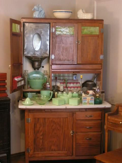 A Hoosier cabinet by Boone, circa 1910 with typical late Victorian kitchen implements. Both original and reproduction parts, fittings, hardware and utensils are widely available for Hoosier cabinets. Check out Hoosier Cabinet, for example.  Four to five feet wide, with built in sugar and flour bins (including a shifter at the bottom), numerous drawers and shelves, spice jars, racks for pots, pans and bowls, a condiment tray, rolling pin rack, cook book holder, and a zinc-lined bread box, the…