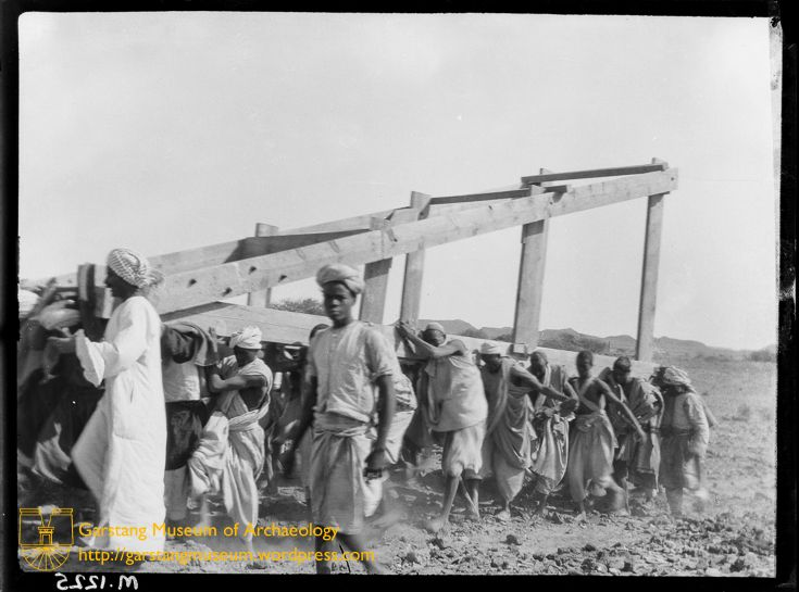 JG-M-A-044 (1912) – Workmen carrying an A-frame, while constructing the aerial railway during the excavations of Meroë.