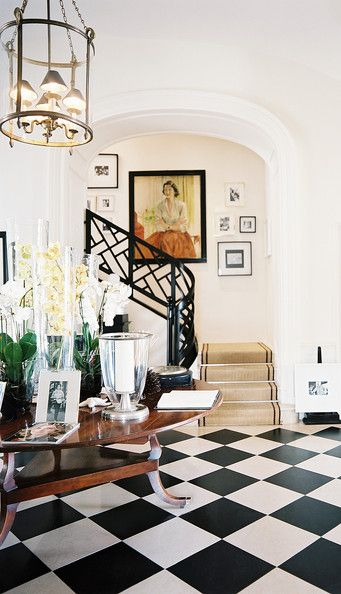 Checkered floors and a round wooden table at the base of a curved staircase