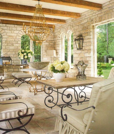 Gorgeous Veranda with wood beams and stone to contrast. The gold metal chandelier pulls the whole room together.