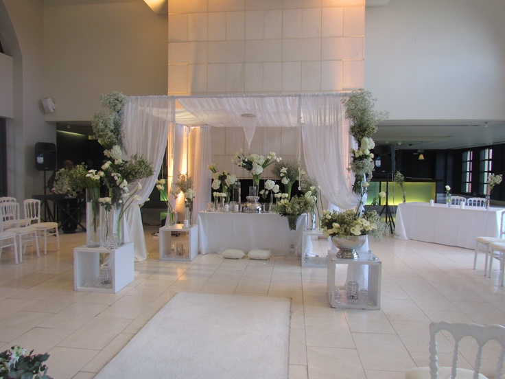 Bringing the traditional arbor back but in style with soft white tulle as the canopy. Incorporating different sizes of clear & silver vases with white flowers on a number of plinths.