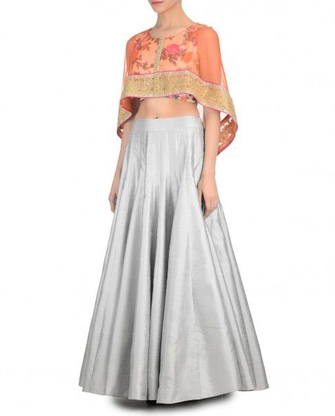 Silver Lehenga with fine pleats. This set comes with a floral printed sleeveless blouse with orange cape style sleeves featuring golden hemline. Round neckline. Wash Care: Dry clean only