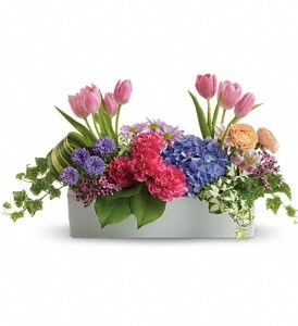 Spring flower arrangement. Filled w/ blue hydrangea, lite pink tulips & alstroemeria, hot pink carnations, orange ranunculus, purple matsumoto asters, lavender daisy spray chrysanthemums and waxflower, Spring greens and ivy are used as fillers.