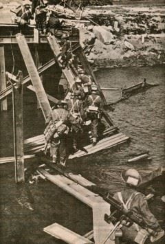 Soldiers of The North Shore Regiment crossing what's left of a bridge near Zutphen towards Germany. Spring 1945.