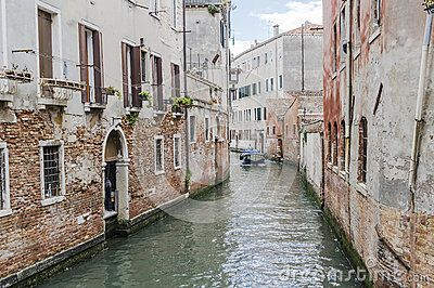 Small canal with motorboats watertaxi in Venice , Italy , Europe.