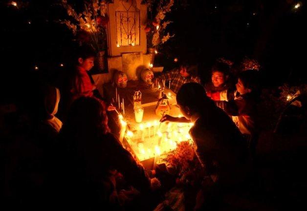 FOR METRO - A family gathers around the grave of relatives Monday Oct. 31, 2005 in the Panteon Municipal in Xoxocotlan, Oaxaca, Mexico during Dia De Los Muertos celebrations. PHOTO BY EDWARD A. ORNELAS/STAFF Photo: EDWARD A. ORNELAS, SAN ANTONIO EXPRESS-NEWS / SAN ANTONIO EXPRESS-NEWS