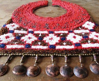 Pectoral bordado a mano con mostacillas de vidrio y monedas de cobre envejecidas.