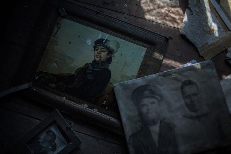 """Black-and-white portrait of a couple who once lived in a now abandoned house in the village of Vorobevo. Beneath the photograph, a reproduction of Ivan Kramskoy's """"The Unknown Woman."""" July 2015."""