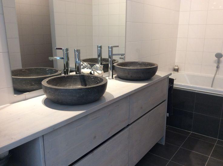 Met oud hout gemaakte badkamermeubel, daarop natuurstenen waskommen.