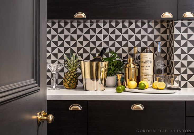 Black and white geometric patterned ceramic wall tiles in office kitchen.