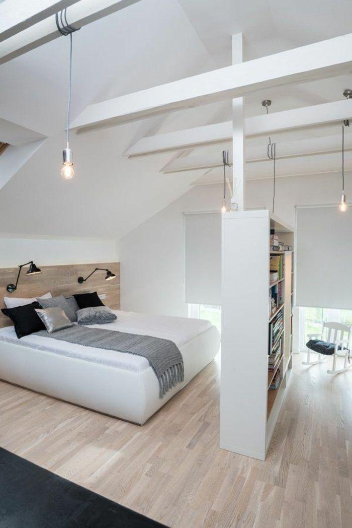 une jolie chambre à coucher avec murs blancs, sol en parquette clair, tapis noir, lit blanc, aménagement de combles