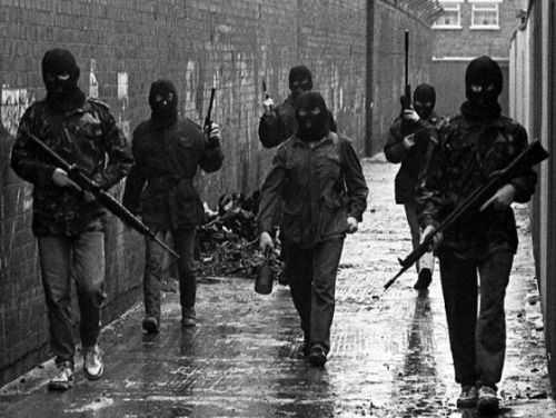 A squad of IRA volunteers moving through a Belfast alleyway. The volunteer in the middle is carrying an anti-tank drogue grenade. Northern Ireland, 1980s.