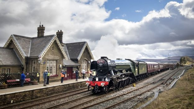 Flying Scotsman passes Ribblehead Train Station in the Yorkshire Dales National Park
