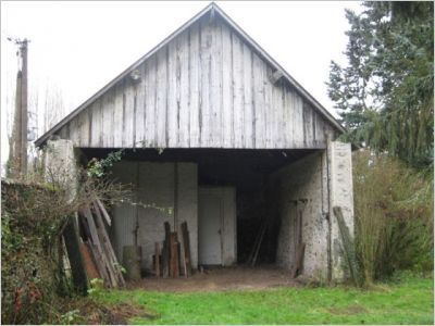 Entourée de verdure, la grange était complètement abandonnée, cette photographie montre la façade arrière du bâtiment.