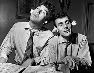 1956 - Eric Sykes (right) and Frankie Howerd playing the piano at Howerd's home in Kensington, London. They were appearing together in the show Pantomania in 1956