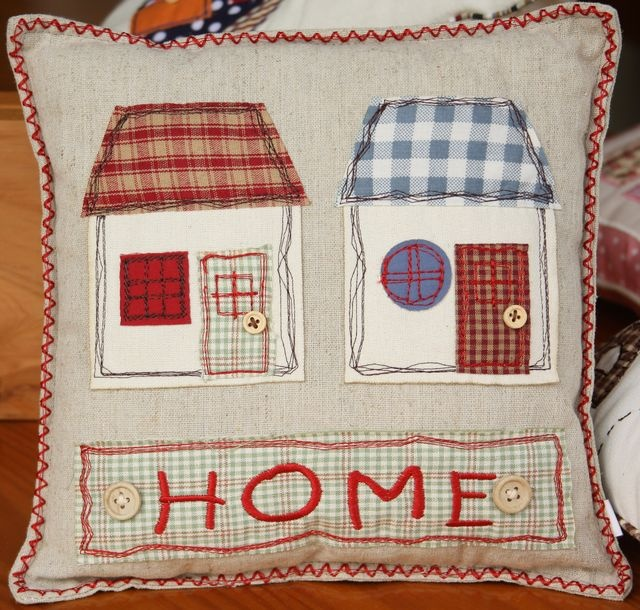 """HOME"" square cushion with appliquéd houses and button detailing – 25cm x 25cm"
