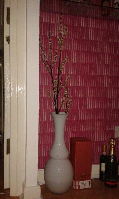 Minimalist flower arrangement against a dramatic wallpaper backdrop.