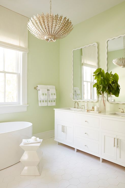 Meg Braff Designs - Restful white and green bathroom boasts celery green walls holding two white scalloped vanity mirrors over a white double washstand fitted with a whtie quartz countertop finished with rectangular sinks paired with polished nickel faucets.
