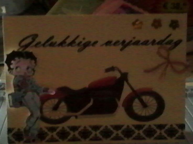 Verjaardagskaart voor mannen. De tekst en de motor zijn afgedrukt op de kaart. Betty Boop is eerst ingekleurd met derwent kleurpotloden en dan uitgeknipt. De kaart is verder afgewerkt met siertape in zwart en wit en gouden bloemen. De strik is gemaakt van koperdraad.