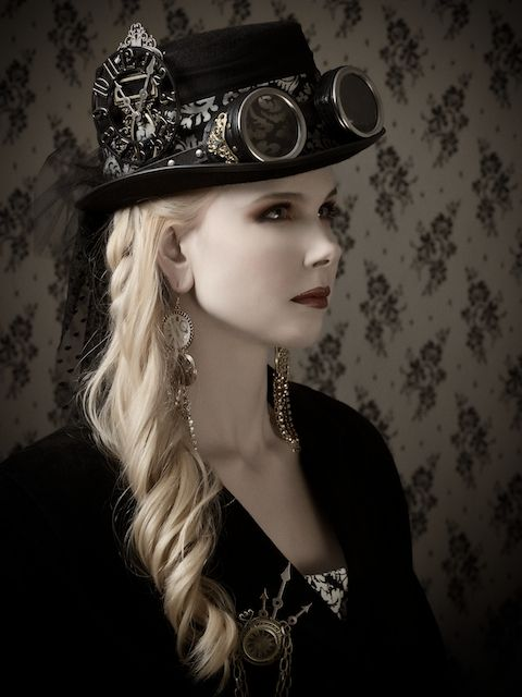 .Steampunk beauty profile with top hat layered with clockwork & goggles & hair softly curled falling down one shoulder.