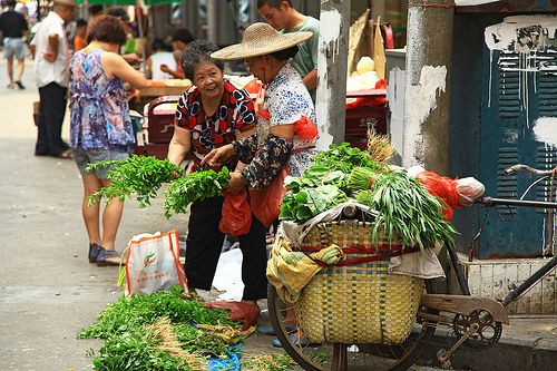 Women selling vegetables at a market in Guangzhou, China.