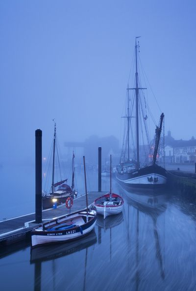 Fog over harbour and boats at dawn, Wells-next-the-sea, North Norfolk Coast, UK