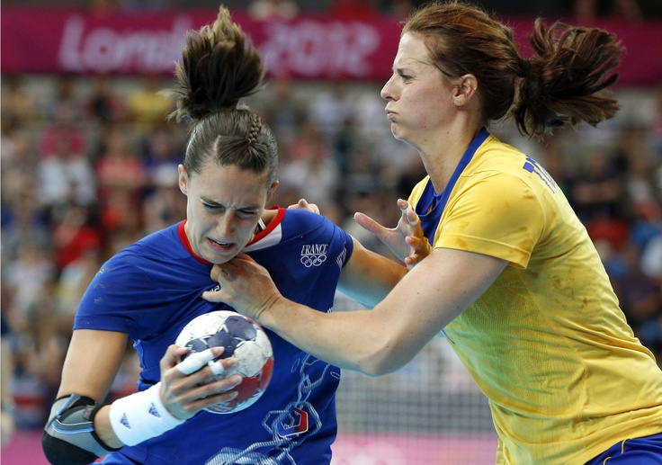 France's Camille Ayglon, left, is challenged by Sweden's Linnea Torstensson, right, during their women's handball preliminary match at the 2012 Summer Olympics, Wednesday, Aug. 1, 2012, in London.