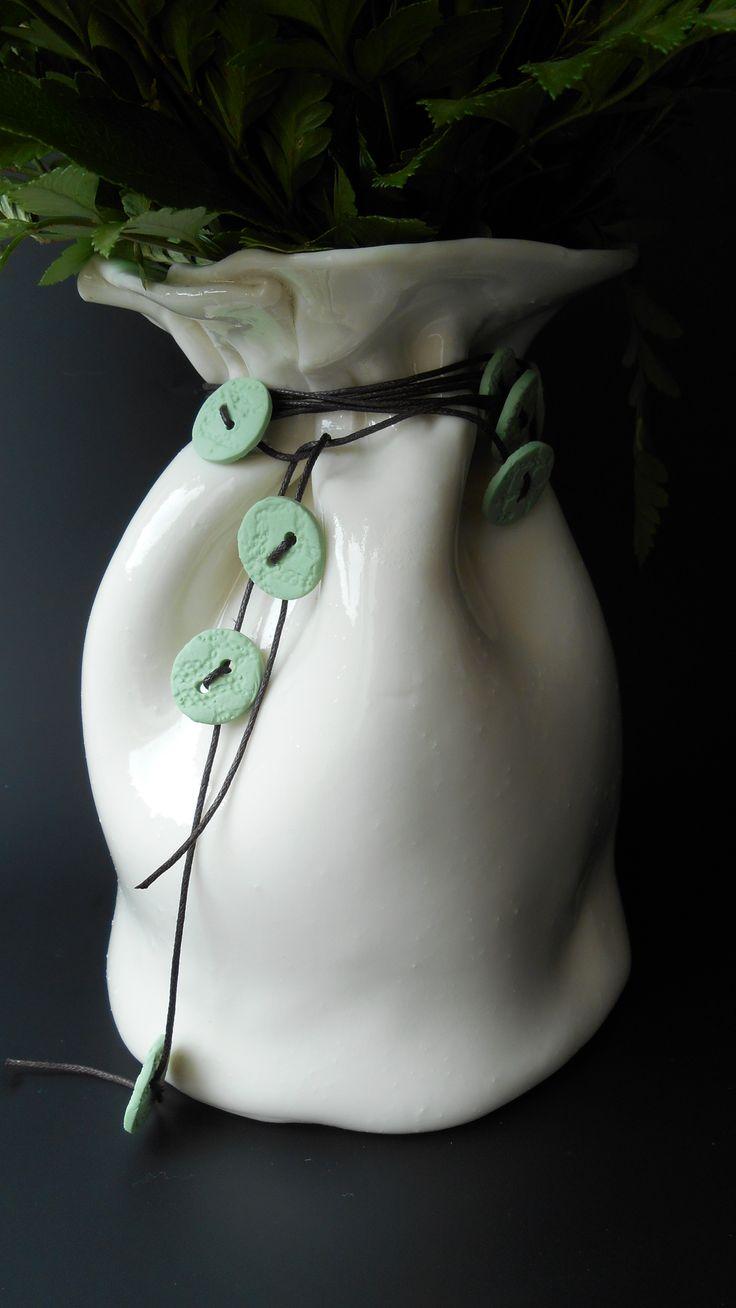 Baggy-vase i porcelænsler med grønne porcelænsknapper i lædersnor omkring.