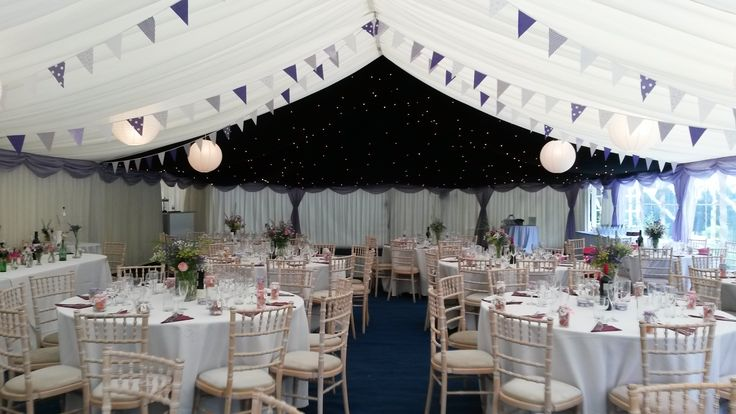 Purple and lilac bunting with lilac pelmets and drapes look fresh and summery in this wedding marquee