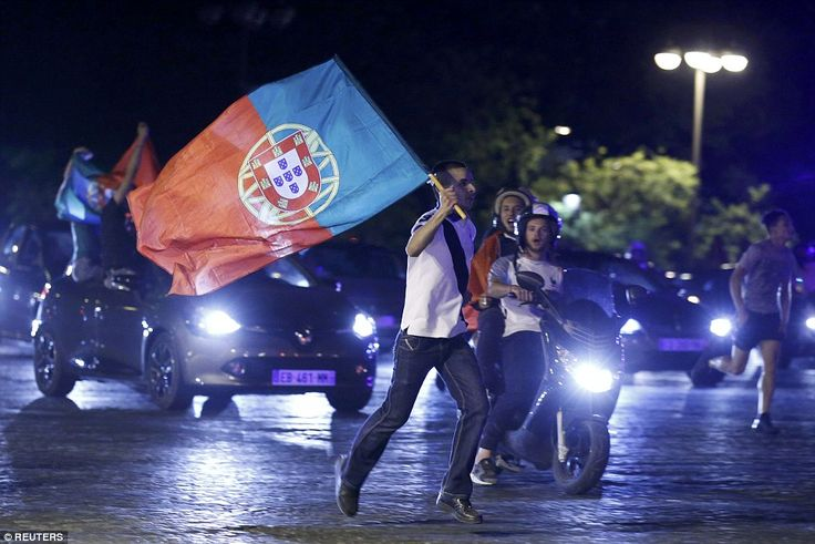 One Portugal fan runs down theChamps-Elysees with theFlag of the Five Escutcheons after ...