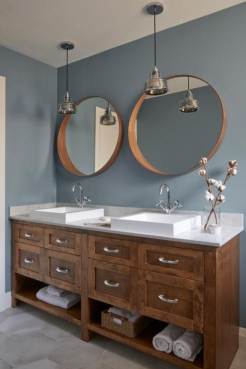 Wonderfully designed blue and brown bathroom boasts brown convex mirrors hung from a blue wall above a brown oak dual washstand fitted with towel shelves and polished nickel pulls and placed on large gray hex floor tiles.
